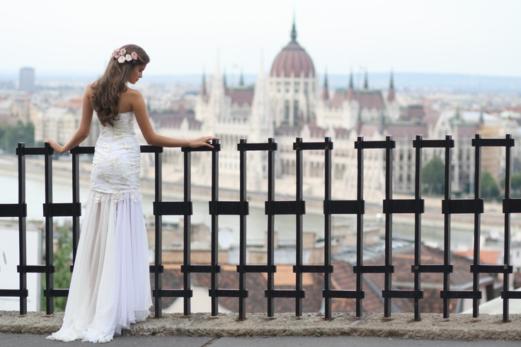 Photo by: Daci - Take a stroll around the sweeping views of Budapest and you will find yourself surrounded by pointed beauty. By using the concrete lines of this harsh fencing, the delicate lace sewn onto the bride's gown and blush pink and satin white flowers garnishing her sweeping locks dazzle.