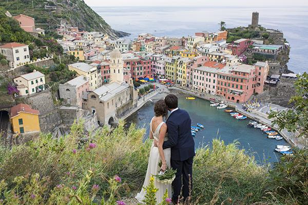 Photo by: Lauren Michelle - These candy-store colors provide the perfect backdrop to make your pictures pop! Having the bride and groom stand in the forefront of the photo gives them heed over this ebullient, little Italian town.