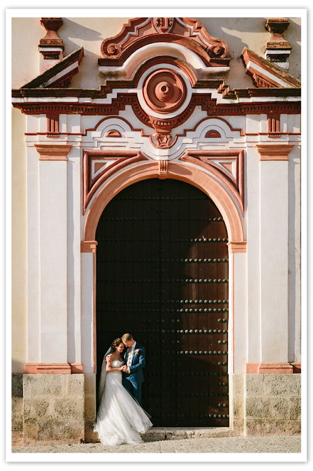Photo by: Joel Bedford - A lively moment caught on film; this Spanish archway is the perfect place for a bold personality and a long lasting memory. With the heavy architecture contrasting with the bride's delicately layered dress and the old-fashioned blue tux, this moment is a picture worth mounting on your mantel.