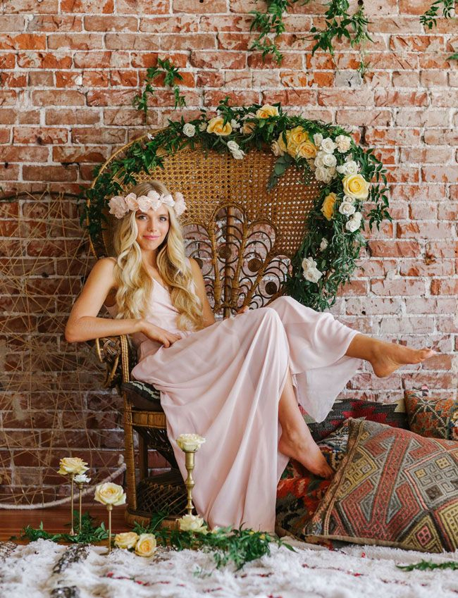 Photo via Joanna August - A bohemian bride in a hand-carved Victorian loveseat may look unusual, but place the barefoot beauty in a rattan peacock chair dripping with greenery and blossoming white and yellow blooms and her playfulness is captured!