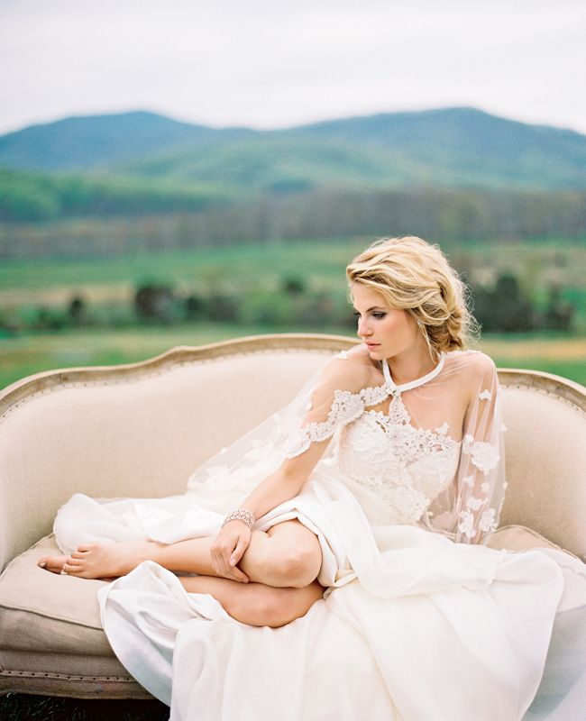 Photo by Eric Kelley Photography - One of the ways this pose works is by removing the bride from the excitement and allowing her to breathe. This thoughtful bride, who is (seemingly) candidly resting shoeless and curled up in her dress on a soft sofa overlooking the land is just divine.