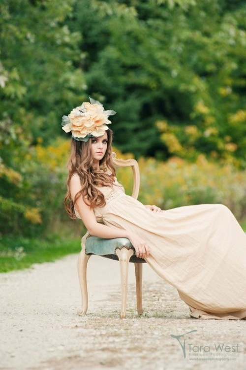 "Photo by Tara West Photography via Blair Nadeau Millinery - Channeling her inner flower child, this bride's effortlessly stunning pose in the center of a dirt road seems to say, ""going my way?"" Her wild locks, oversized floral headdress, and natural-colored cloth dress add a sense of whimsical 1960s wonder."
