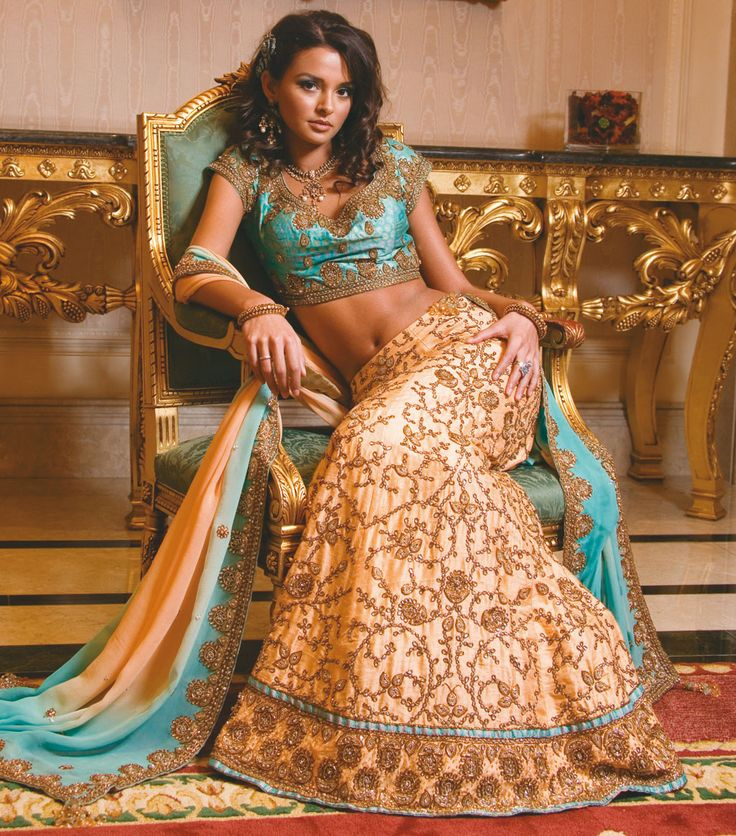 Photo via Sonas Couture - The sitting pretty pose isn't just for stealing a moment with a bride to capture her excitement alone - it's also about showing off! We adore this bride (and photographer) for finding the beautiful hand carved, giltwood table and chair that perfectly compliment the ornate embroidery and turquoise color of her gorgeous gown. Wow!