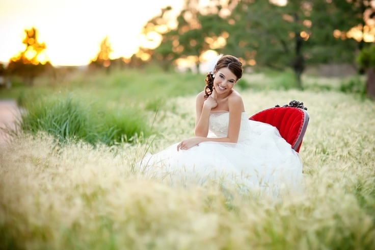Photo by Keri Doolittle Photography - Look at the field as rippling waves of grass and greenery for a moment. There in the middle is our beautiful pearl of a bride, seated casually in her ruby red oyster shell style settee, the focal point of the photograph with color, focus, and pose.