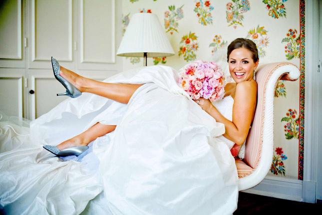 Photo by True Photography Weddings - A sweet and joyful memory, this bride exudes an obvious joie de vivre in this playful lounge pose. With an opportunity like this, what bride wouldn't want to kick up her feet and celebrate!