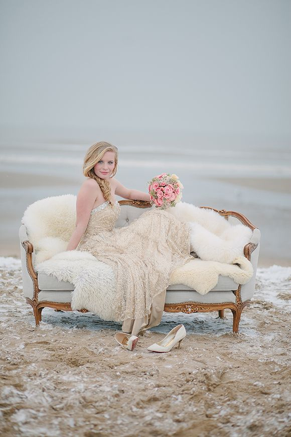 Photo by Jennifer Hejna - With a handcrafted loveseat and layers of luxurious cream and beige-colored fur, silk, and lace fabrics, this beautiful bride brings warmth into a cool shoreside photo.