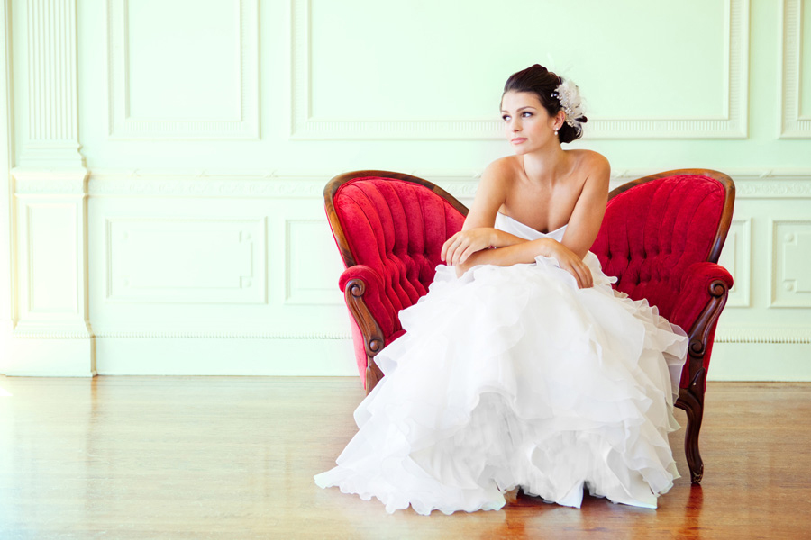 Photo via Skyla Arts - Taking advantage of an empty corner adds the contrast one needs to capture this classic photograph. From the red tufted loveseat placed away from the wall, to the white tulle of the bride's dress, and from the pale mint-green molding of the great wall, to the polished wood floors, each contrasting color and pattern plays an integral role in highlighting her beauty.