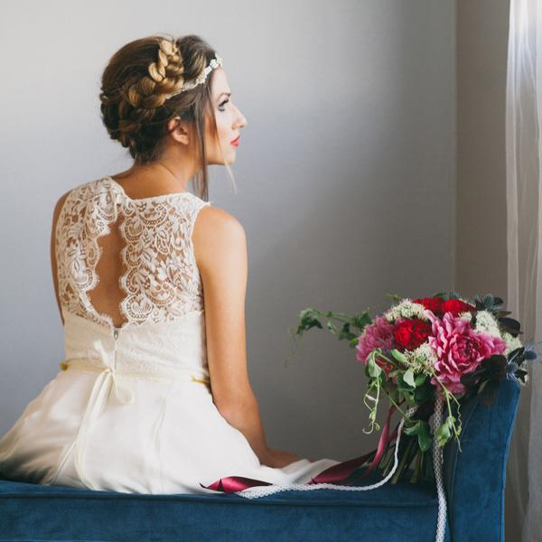 Photo by Alexandra Wallace Photography - The blue velvet bench and rich red and pink bouquet draw just enough attention away from the backward-facing bride so that you feel you've captured a private thought. This pose is a brilliant way to show off a wedding gown's decorative back.